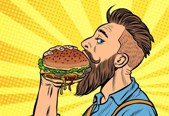 Un homme mange un hamburger